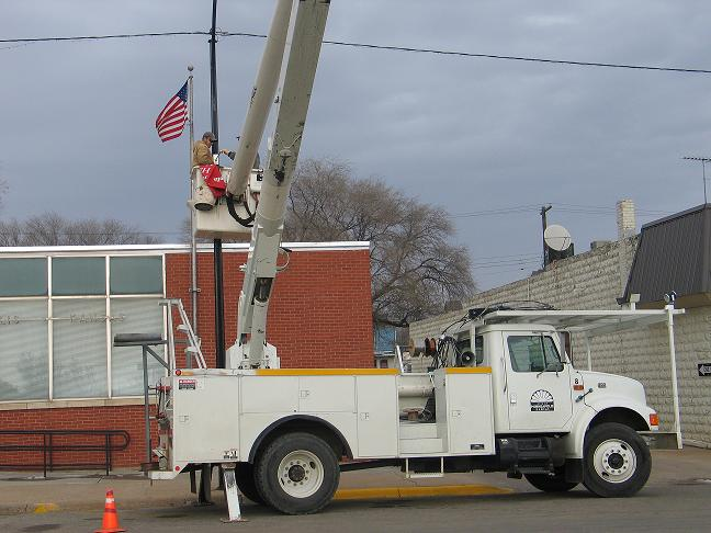 City employees in a telehandler as they fix power lines.